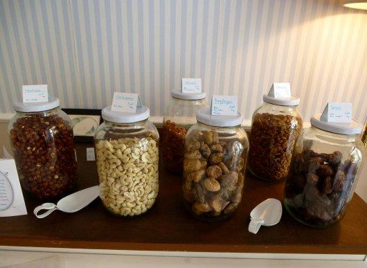Krüge mit Haselnüssen, Cashewkernen, Mandeln, Bergfeigen, Pekannüssen und Datteln im Tilia's